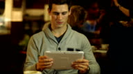 Young Man using Digital Tablet in Cafe / Coffee shop