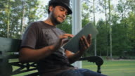 MS LA Young man using digital tablet outdoors / Madison, Florida, USA