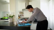 MS Young man using laptop and smartphone in kitchen