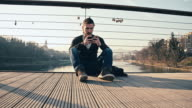 WS Young Man Using Smart Phone On Bridge