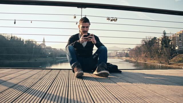 WS junger Mann mit Smartphone auf Brücke