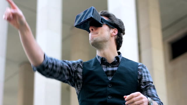 Young man using virtual reality outdoors