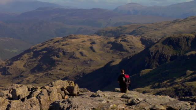 WS Young man walking down mountain, Lakeland fells in background / Lake District, Cumbria, UK