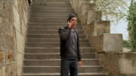 WS TD PAN Young man walking down stairs while talking on phone, Paris, Ile de France, France