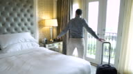 Young man walking into a hotel room and falling in bed
