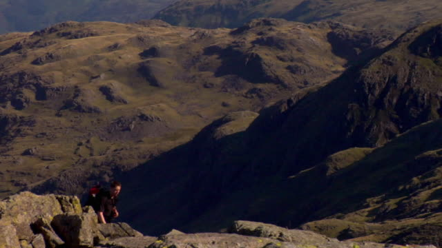 WS Young man walking up mountain past with Lakeland fells in background / Lake District, Cumbria, UK