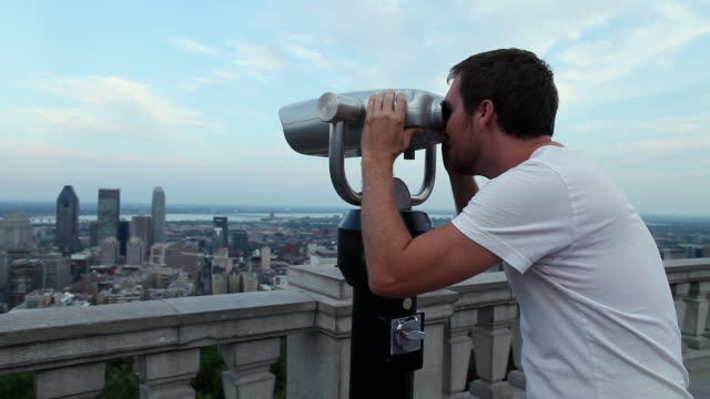 MS Young man walking up to binoculars and looking through binoculars at montreal skyline from top of Mount Royal / Montreal, Quebec, Canada