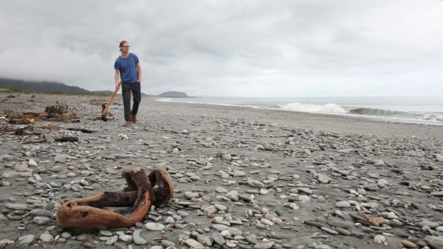 Young man walks along beach on cloudy day, beachcombing