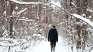 Young man walks on a snowbound trail in the forest.