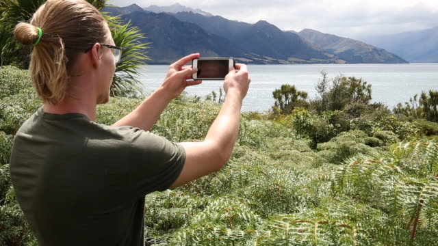 Young man walks through ferns and takes pic, mountains ranges