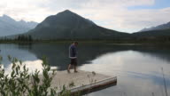 Young man walks to edge of mountain lake, takes picture