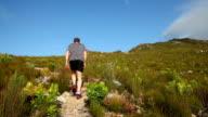 Giovane uomo che cammina su un sentiero percorso di montagna