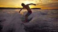 Young man wave surfing behind a boat at sunset