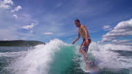Young man wave surfing behind a boat