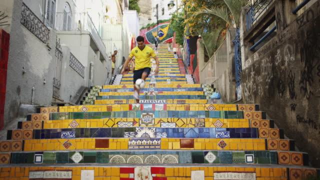 WS, TU A young man wearing a Brazil t-shirt practices football skills on Selaron Steps (Escadaria Selaron) / Rio de Janeiro, Brazil