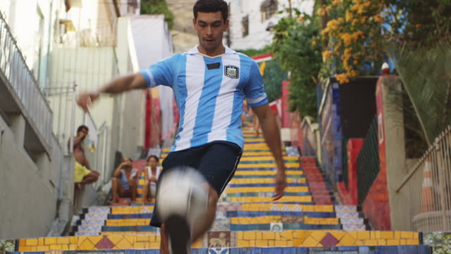 MS A young man wearing an Argentina t-shirt practices football skills on Selaron Steps (Escadaria Selaron) / Rio de Janeiro, Brazil