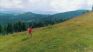 Jonge man met rugzak en Polen lopen op bergpad