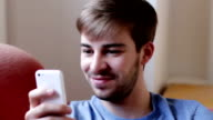 Young man with beard and glasses texting.