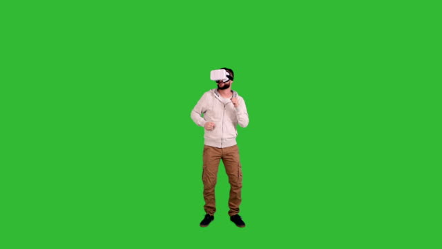 Young man with glasses of virtual reality dancing on a green
