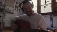MS SLO MO. Young man with headphones sings and plays guitar in sunny apartment studio.
