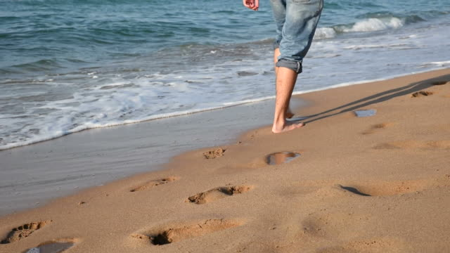 Young Man With Jeans Walking From The Beach