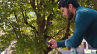 Young Man With Smart Phone in an Outdoors Park