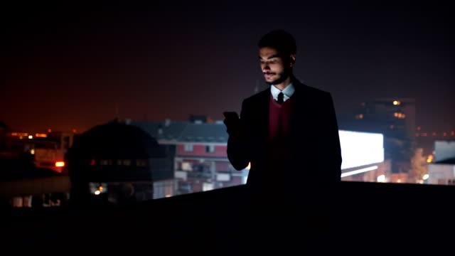 Jonge man met smartphone op dak