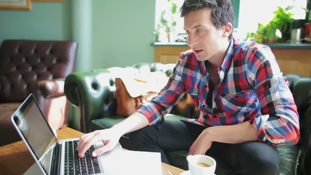 Young man working at his laptop in coffee shop.
