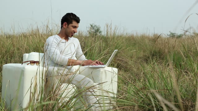 Young man working on a laptop in the forest