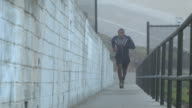 A Young man working out and running on a steep ramp by the beach.