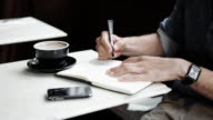 Young man writing in coffee shop