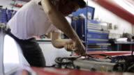 MS Young mechanic working on car inside  garage / Bayport, Minnesota, United States