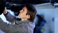 Giovane meccanico Lavora sotto auto