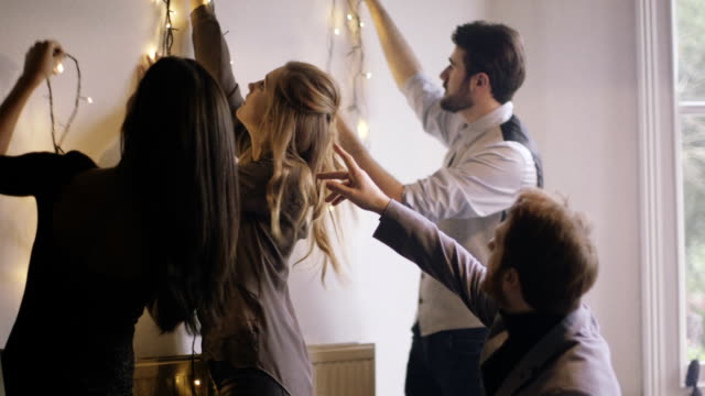 Young men and women decorating wall with lights for Christmas party