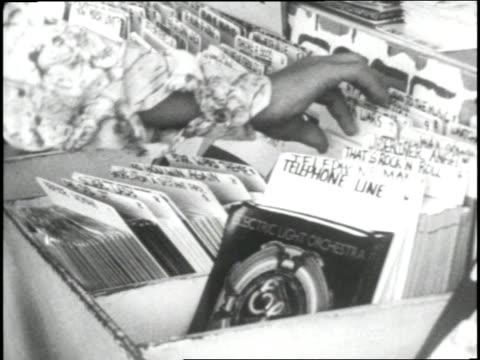 Young men and women shop through numerous record bins for record albums at a music store