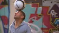 CU PAN Young men bouncing soccer ball on head near graffiti wall, London, England, UK