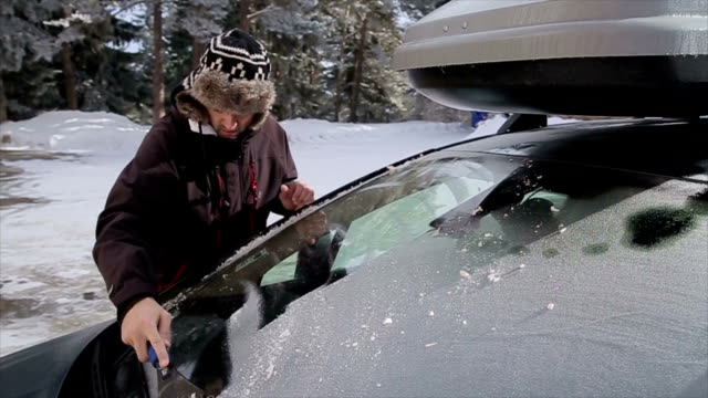 Young men Cleaning the car from the snow