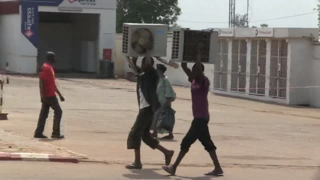 Young men hastily carry fans while another group of men push a stolen car through the capital of the Central African Republic on Saturday as looting...