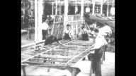 Young men in factory maneuver the wooden skeleton of a WWI biplane's wing as two others paint glue on the edge / Men construct and string wire...