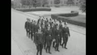 Young men in police uniforms run from building and jump into transport trucks covered with tarps / VS police officers marching in unison past camera...