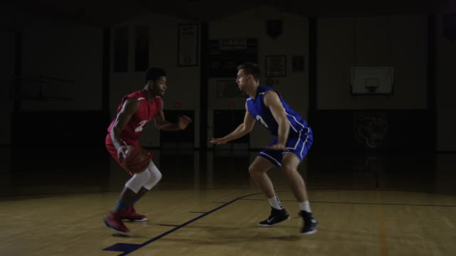 Young men playing basketball defending each other