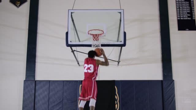 Unga män slam dunking en basketboll