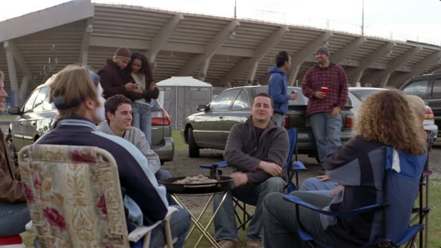 Young men tossing football around grill at tailgate party / couple in background text messaging on cell phone and two young men holding cups of beer and talking