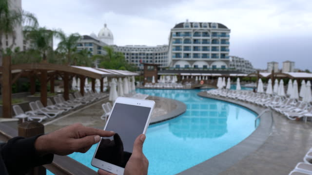 Young men using digital tablet in resort