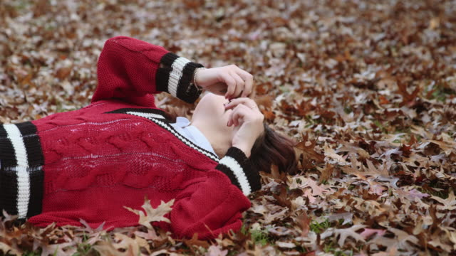 A young millennial woman playing with autumn leaves
