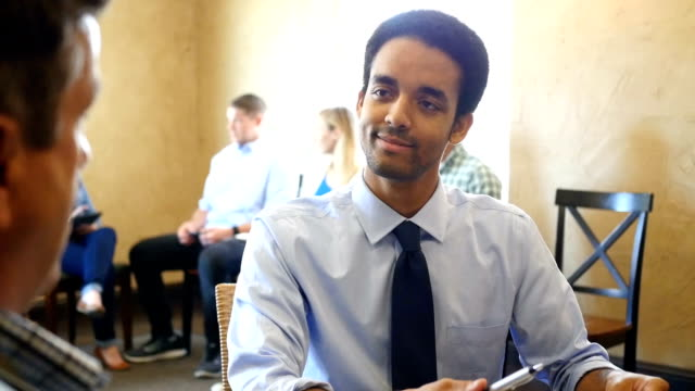 Young mixed race businessman interviews potential employee