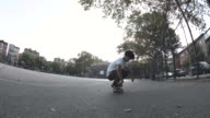 A young, mixed race man skateboards in the streets of Brooklyn