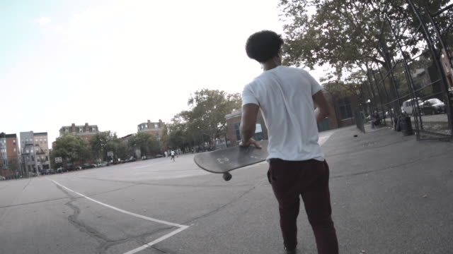 A young, mixed race man walks with his skateboard in the streets of New York City