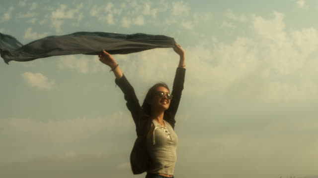 A young mixed race woman flies her scarf in the wind.