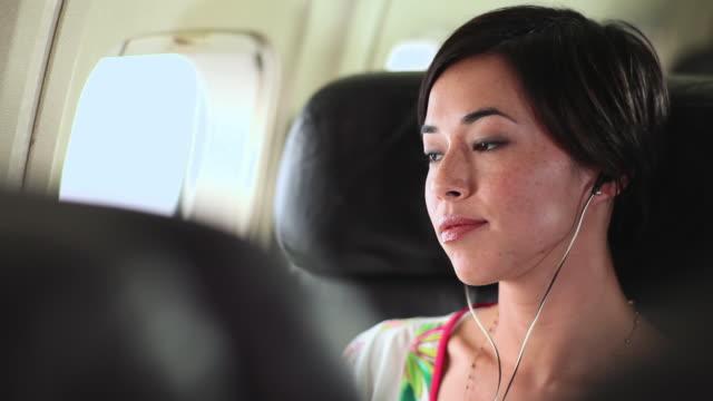 Young mixed race woman sitting on aeroplane